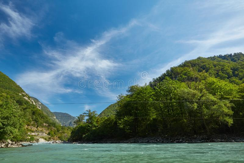 Landscape with mountains, forest and a river in front royalty free stock images