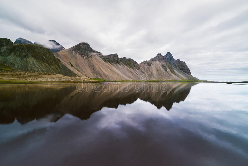 Landscape with mountains reflected in water, Iceland. Amazing landscape of mountains reflected in the water the Bay. View of Cape Stokksnes in the southeastern stock image