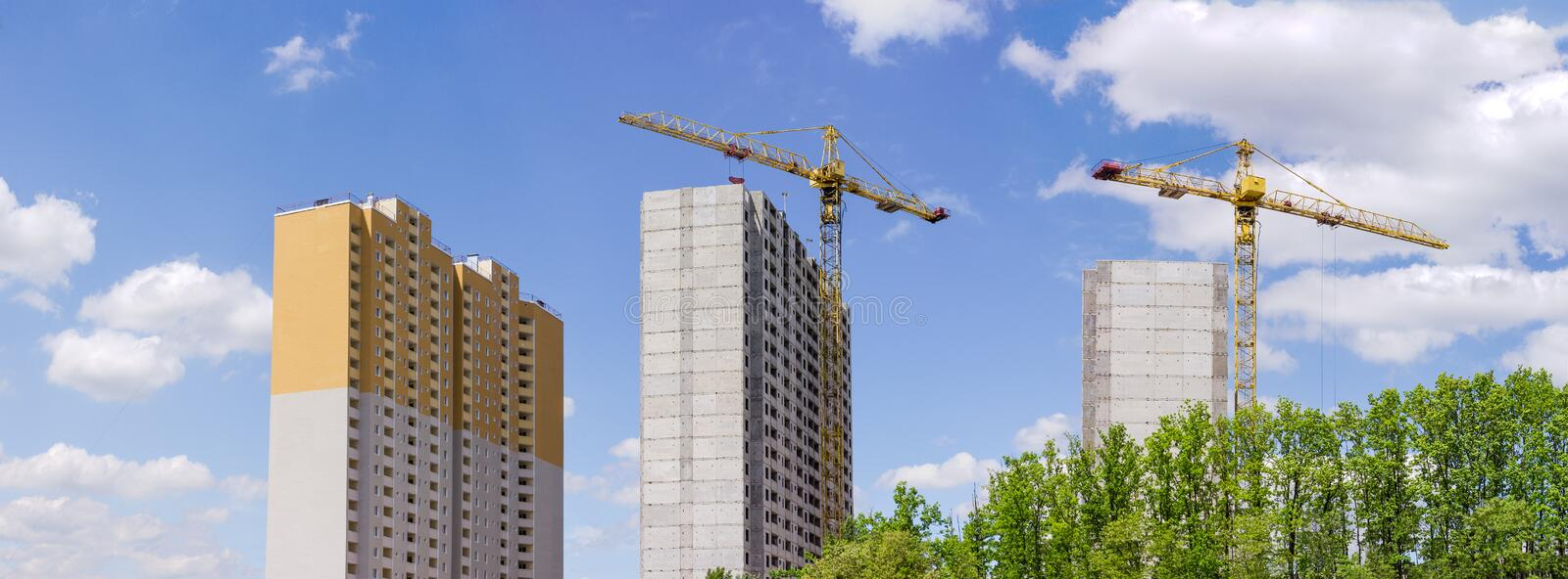 Landscape with multi story houses under construction and building cranes. Panorama of the construction of the multi story residential houses from precast stock photography