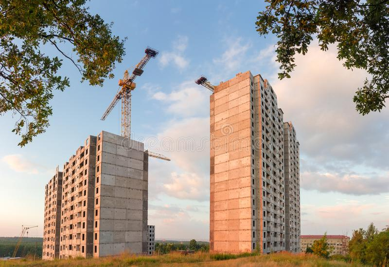 Landscape with multi story houses under construction at sunset. Panorama of the construction of the multi story residential houses from precast concrete panels royalty free stock photography