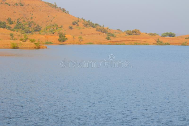 Landscape in nature, mahi back water, banswara, rajasthan, India. Beautiful brown mountain, river blue water and green tree on mountain providing natural beauty royalty free stock photos