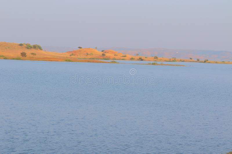 Landscape in nature, mahi back water, banswara, rajasthan, India. Beautiful brown mountain, river blue water and green tree on mountain providing natural beauty royalty free stock photo