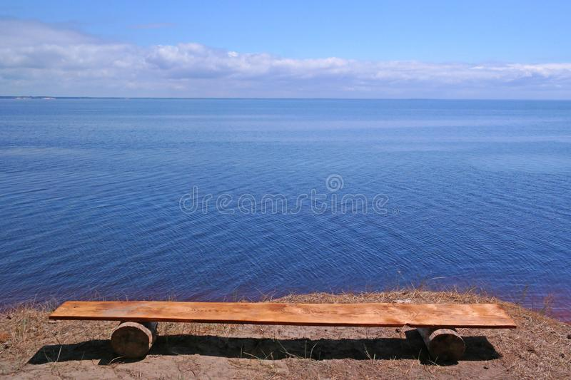 Wooden bench by the river royalty free stock images