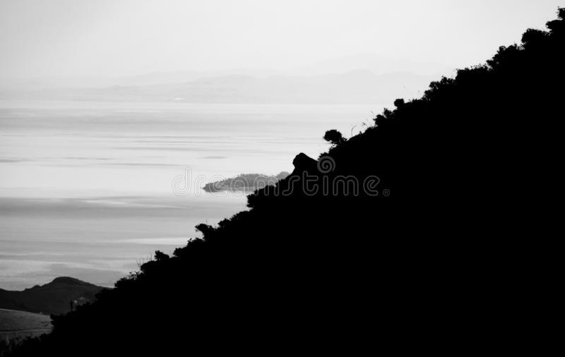 Landscape of the near mountain peak, foggy lake, island and mountain background. Black and white photography stock photography