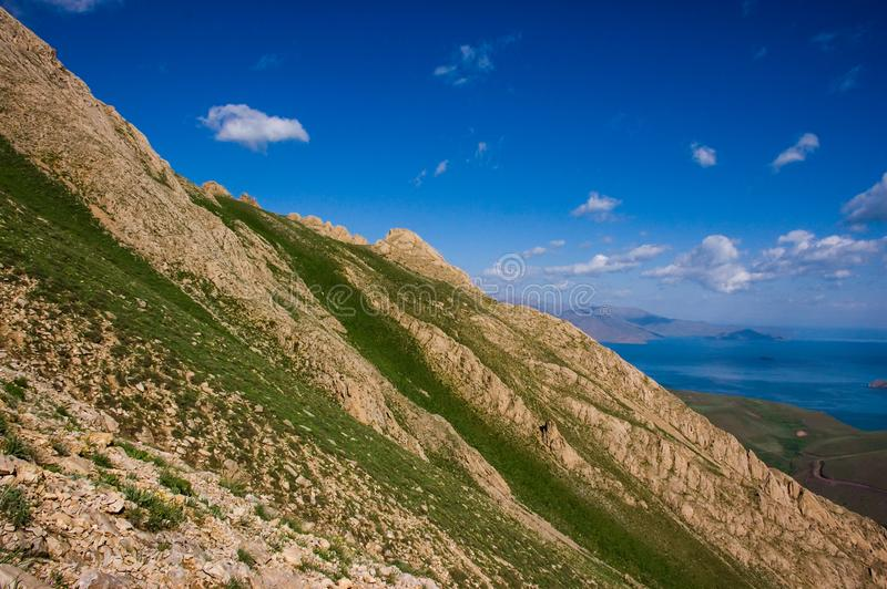 Landscape of the near mountain peak. Lake, cloudy sky background royalty free stock photo