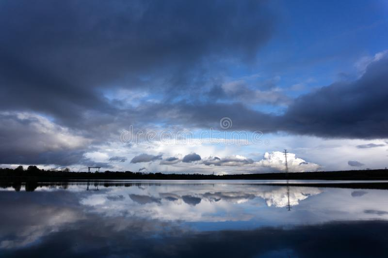 Landscape of night sky. Beautiful bright full moon and cloudy above silhouettes of trees, river area. Serenity nature background. stock photo