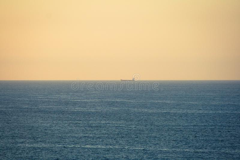 Tanker ship sailing through the sea at sunset. Landscape of an ocean with the horizon line centered on the image, a tanker sailing and an orange sky at sunset stock images
