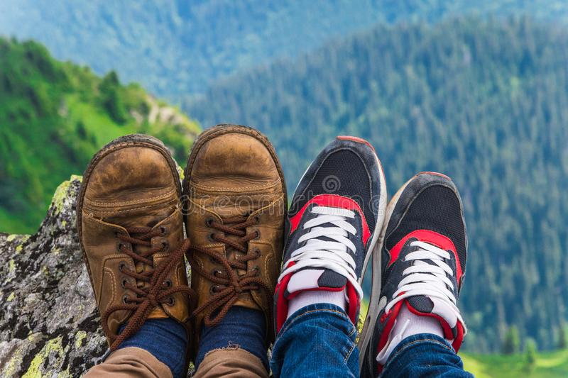 Landscape, travel, tourism. A pair of feet in the shoes against the background of the mountains. Horizontal frame. Landscape. A pair of feet in the shoes against stock photography