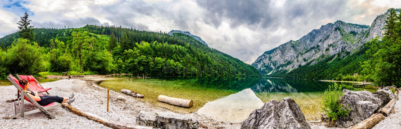 Landscape panorama with woman on sunbed next to the lake Leopoldsteinersee,Styria,Austria. Travel destination Austria. Landscape panorama with woman on sunbed royalty free stock photos