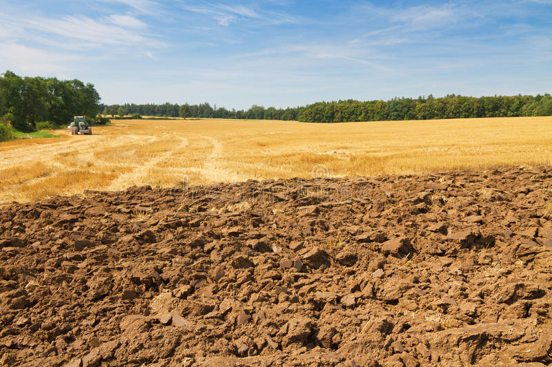 Landscape with partly ploughed field and stubble royalty free stock photo