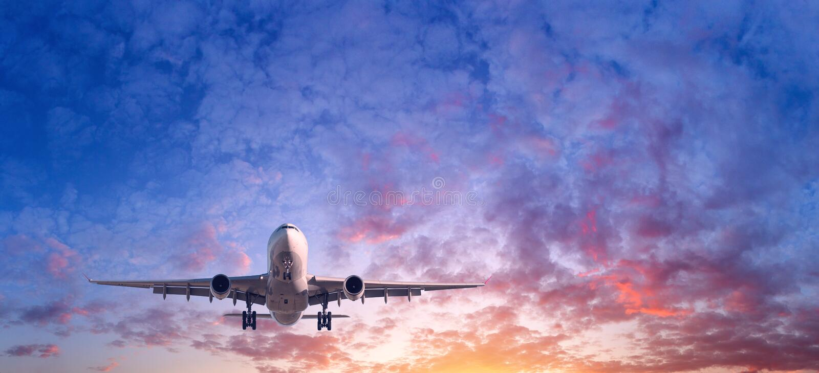Landscape with passenger airplane is flying in the blue sky. Landing airplane. Landscape with passenger airplane is flying in the blue sky with red, purple and royalty free stock photography