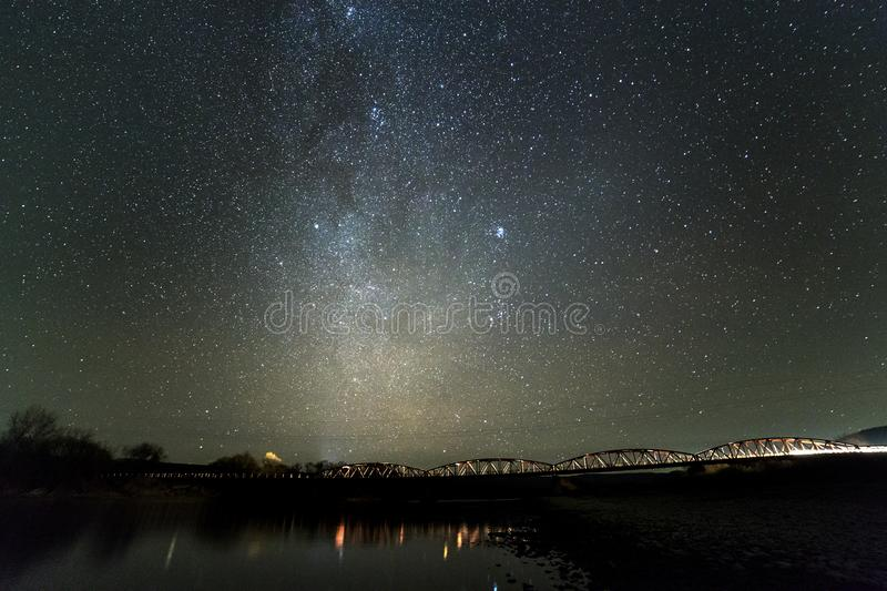 Landscape of pebbles river bank, trees on horizon, bright stars and Milky Way galaxy in dark sky reflected in quiet water. Beauty royalty free stock image