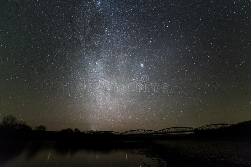 Landscape of pebbles river bank, trees on horizon, bright stars and Milky Way galaxy in dark sky reflected in quiet water. Beauty stock photography