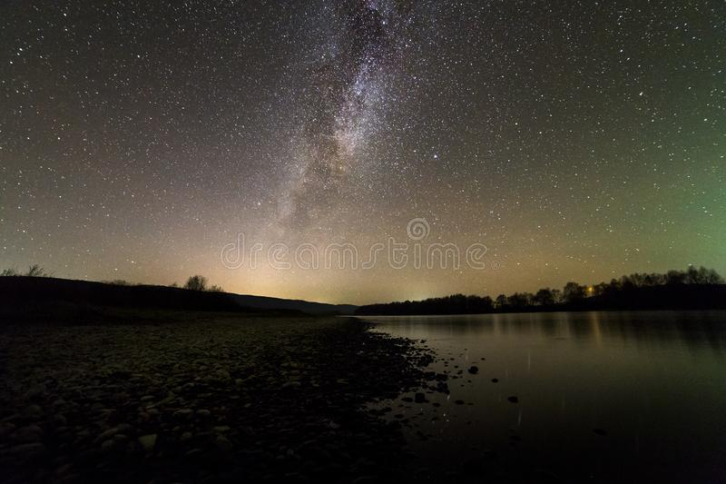 Landscape of pebbles river bank, trees on horizon, bright stars and Milky Way galaxy in dark sky reflected in quiet water. Beauty royalty free stock photography