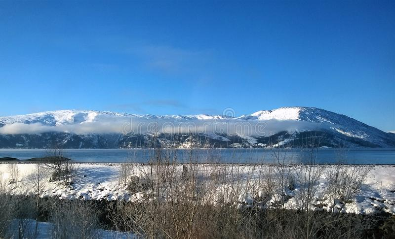 Landscape Photo of Body of Water Within Snow Coated Mountain Range royalty free stock image