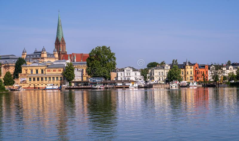 A Landscape Photo of Schwerin Germany. A landscape photo of the city of Schwerin, Germany by the water with buildings reflected in the lake stock photo