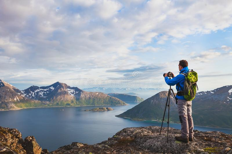 Landscape photographer working with tripod and dslr camera. In beautiful wild nature, standing with backpack on top of mountain stock photos