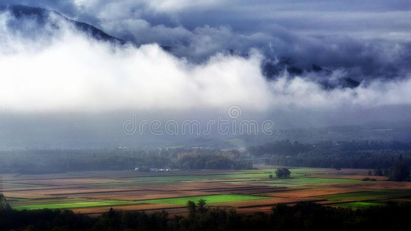 Landscape Photography of Green and Brown Rice Field Surrounded With White and Blue Clouds Near Black Mountains stock photos