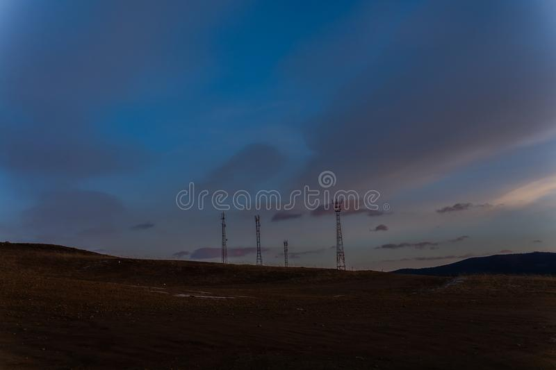 Landscape photography of hill at twilight, telecommunication pole on hill stock photo