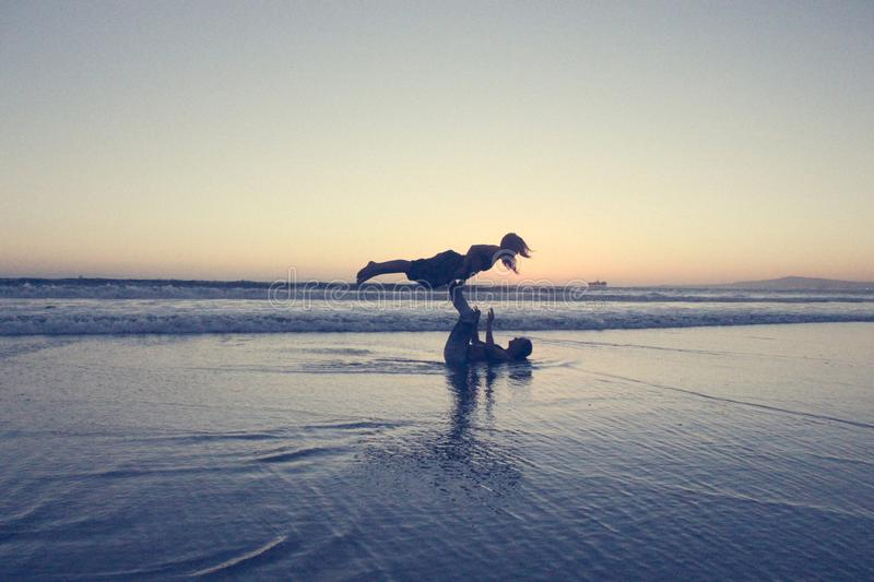 Landscape Photography of Man Lifting Woman by His Foot on Seashore royalty free stock photography