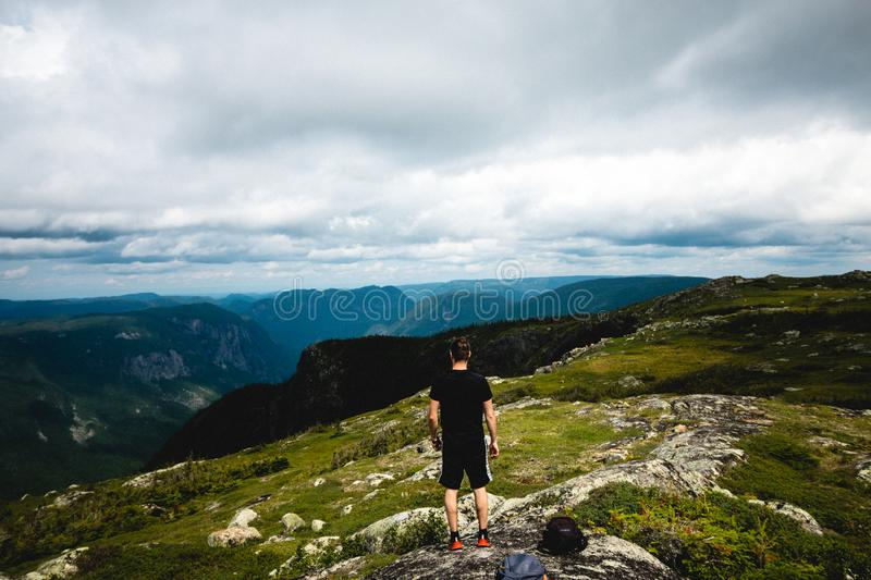 A landscape photography with mountains and clouds. A landscape photography of Charlevoix, Quebec, Canada. Man standing in from of the mountains royalty free stock image