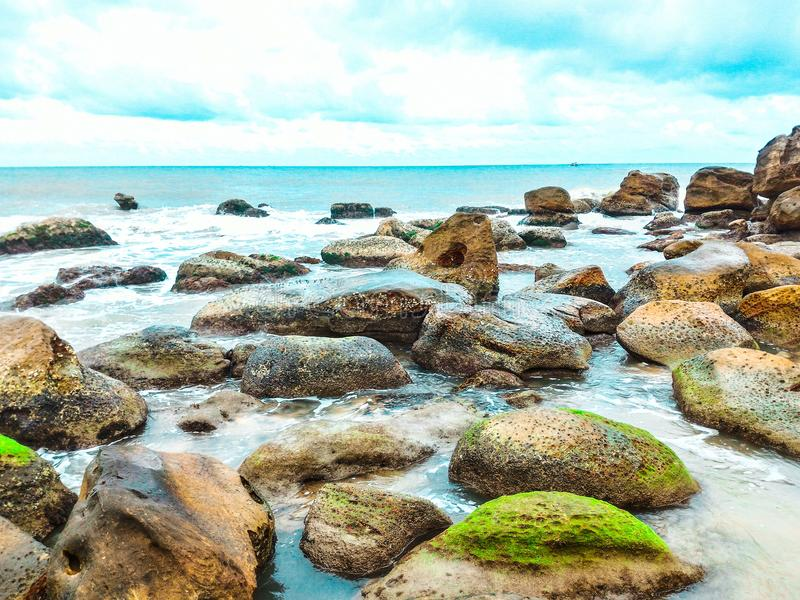 Landscape Photography of Rocks With Moss Surrounded by Body of Water stock photos
