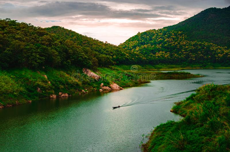 Landscape picture of river, mountain, forest, fishing boat and stock image