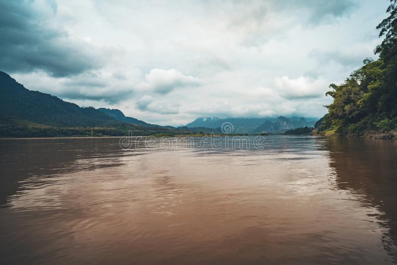 A landscape pictures of the shores of the mekong river in south vietnam near vinh long on a sunny summer day. Mountain in clouds. The landscape of Laos stock photo