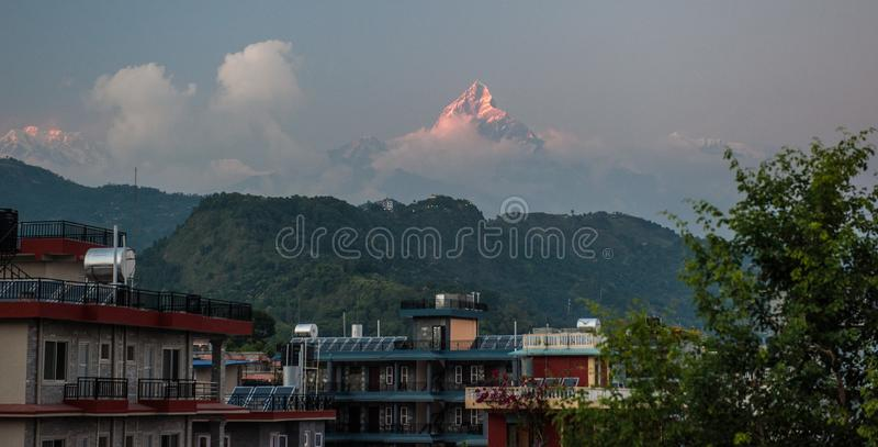 Landscape with Pokhara rooftops on sunrise with Annapurna South, Hiunchuli and Machapuchare Fishtail Peaks in background. Himalaya royalty free stock images