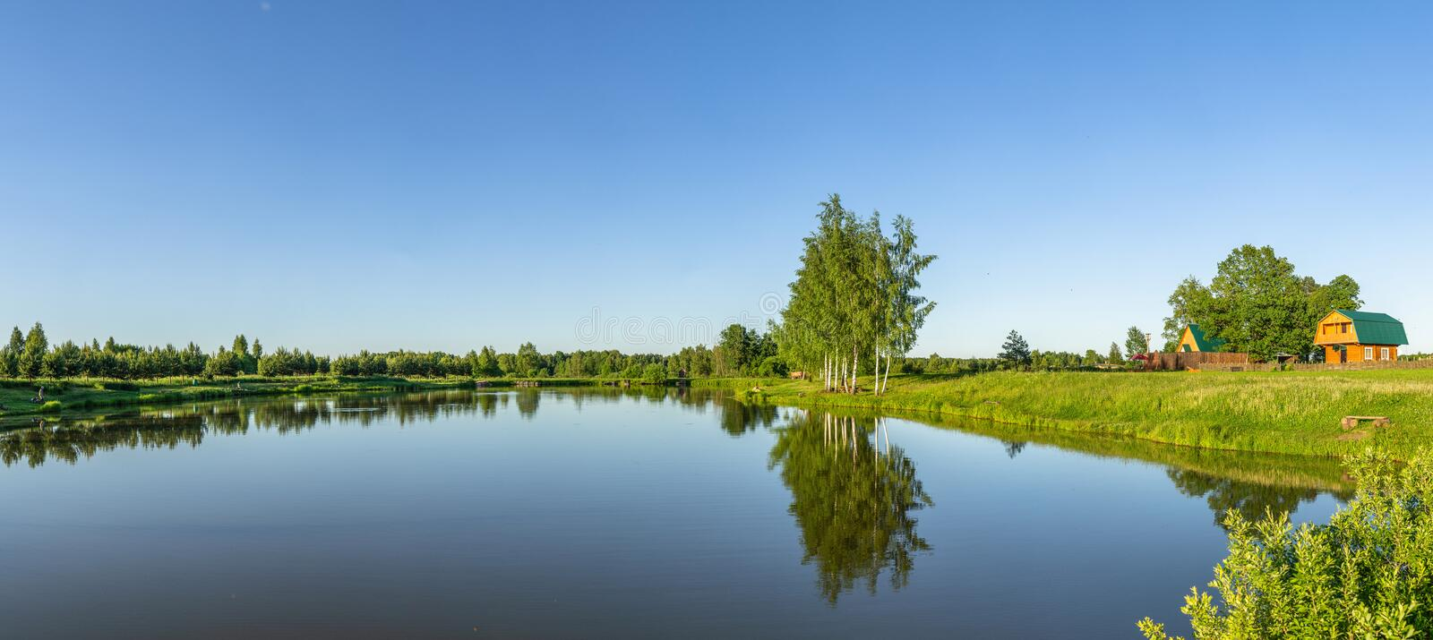 Landscape with a pond at sunset in Central Russia. The landscape at sunset is rich in colors. Illuminated by Golden sunlight, fields, meadows, trees, hills and royalty free stock image