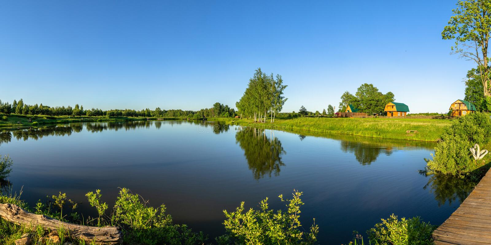 Landscape with a pond at sunset in Central Russia. The landscape at sunset is rich in colors. Illuminated by Golden sunlight, fields, meadows, trees, hills and royalty free stock photos