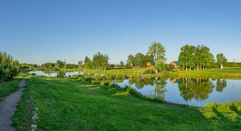 Landscape with a pond at sunset in Central Russia. The landscape at sunset is rich in colors. Illuminated by Golden sunlight, fields, meadows, trees, hills and royalty free stock photo