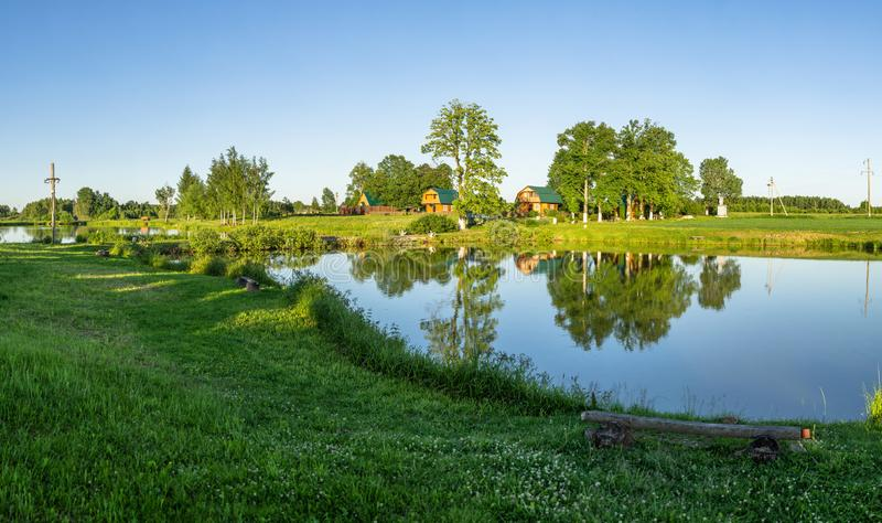 Landscape with a pond at sunset in Central Russia. The landscape at sunset is rich in colors. Illuminated by Golden sunlight, fields, meadows, trees, hills and stock images