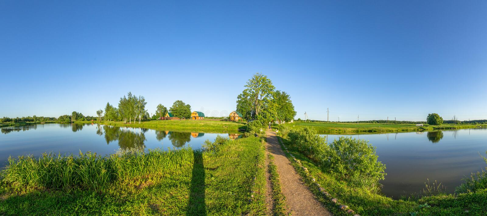 Landscape with a pond at sunset in Central Russia. The landscape at sunset is rich in colors. Illuminated by Golden sunlight, fields, meadows, trees, hills and stock photos