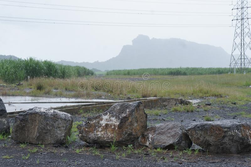 View of the mountain `Sleeping woman` from the highway on the island of Mauritius. Landscape in the rain with the mountain `Sleeping woman` on the island of stock image