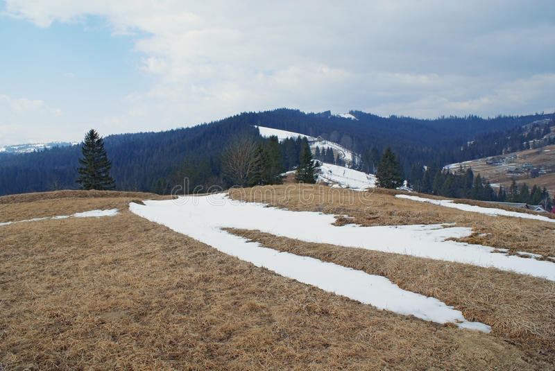 Landscape remnants of snow in meadow on slopes of a mountain range stock images