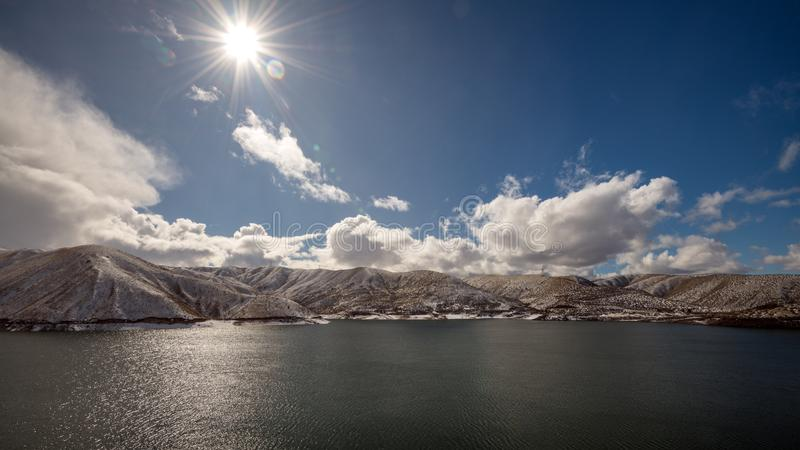 Sun star over Lucky Peak reservoir with snow and clouds royalty free stock image