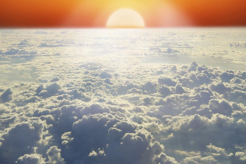 Landscape with rising sun above horizon and white cloud. Bright sun above clouds stock photo