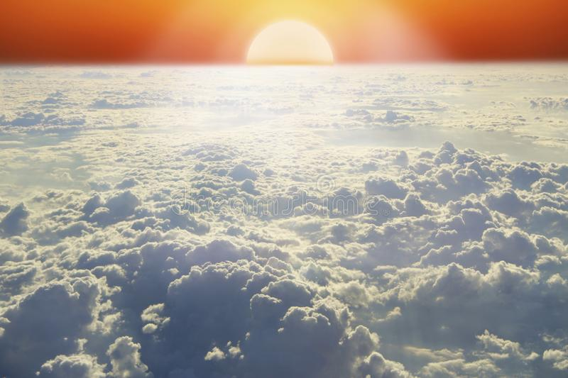 Landscape with rising sun above horizon and white cloud. Bright sun above clouds royalty free stock photo