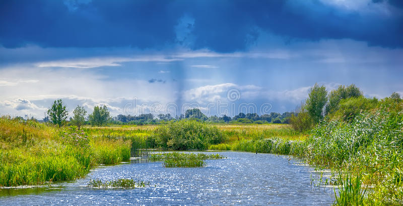 Landscape with river, clouds and rain in the sky. stock photography