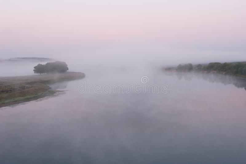 Landscape on the river Desna. Morning misty landscape on the river Desna, Ukraine. A lot of fog over the water, a pink sky, two beaches stock image