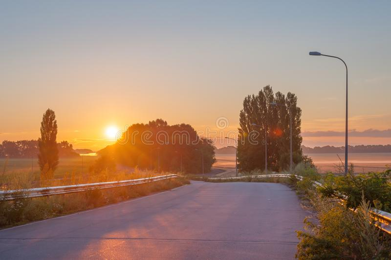Landscape with road. Morning landscape with road and rising sun royalty free stock photo