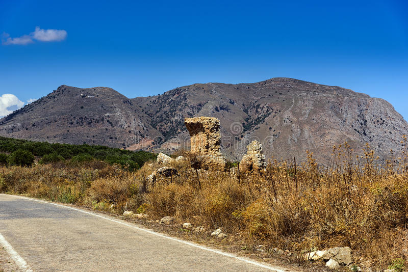 Landscape with road, mountains and old ruins at Crete island, Greece royalty free stock image