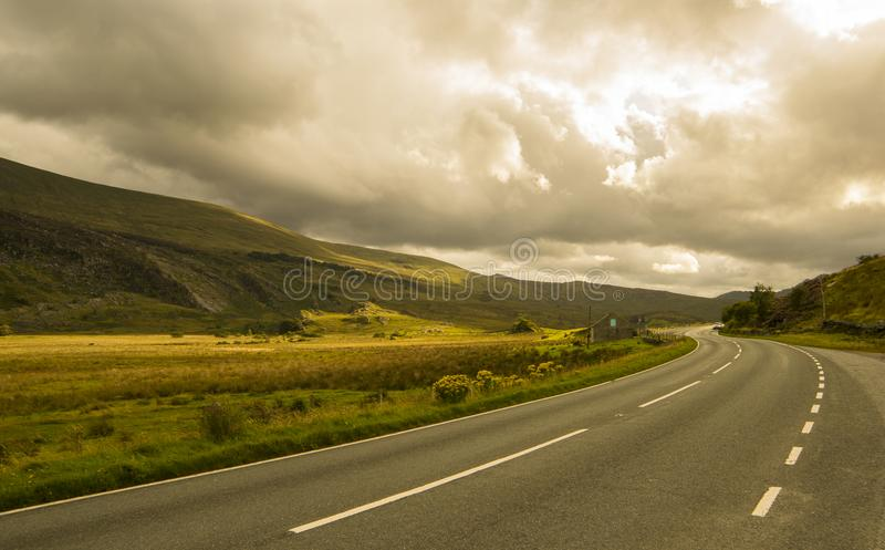Landscape road in mountains. Landscape road in mountains under cloudy sky royalty free stock photography