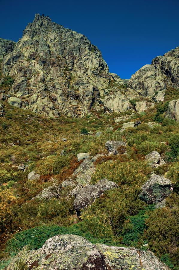 Landscape with rocky cliffs covered by green bushes. Mountainous landscape with rocky cliffs covered by green bushes, at the highlands of Serra da Estrela. The stock images