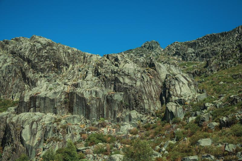 Landscape with rocky cliffs covered by green bushes. Mountainous landscape with rocky cliffs covered by green bushes in a sunny day, at the highlands of Serra da royalty free stock photos