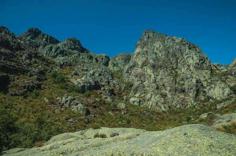 Landscape with rocky cliffs covered by green bushes. Mountainous landscape with rocky cliffs covered by green bushes in a sunny day, at the highlands of Serra da royalty free stock photo