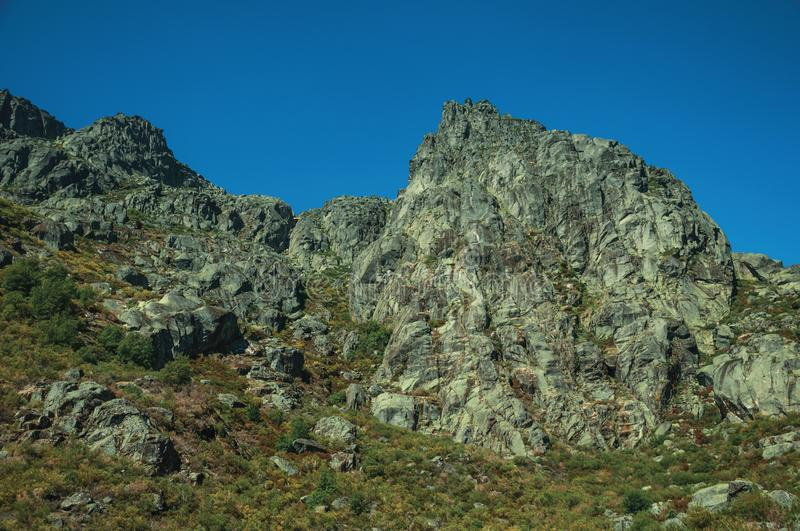 Landscape with rocky cliffs covered by green bushes. Mountainous landscape with rocky cliffs covered by green bushes in a sunny day, at the highlands of Serra da stock photos