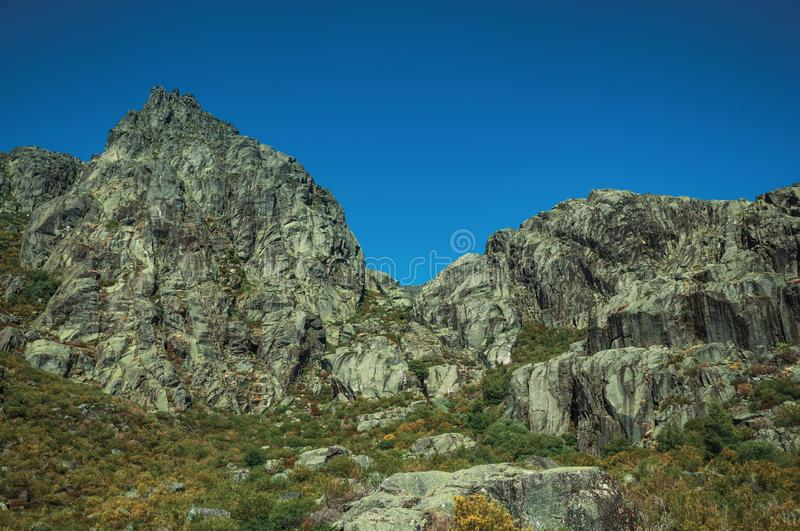 Landscape with rocky cliffs covered by green bushes. Mountainous landscape with rocky cliffs covered by green bushes in a sunny day, at the highlands of Serra da royalty free stock photography