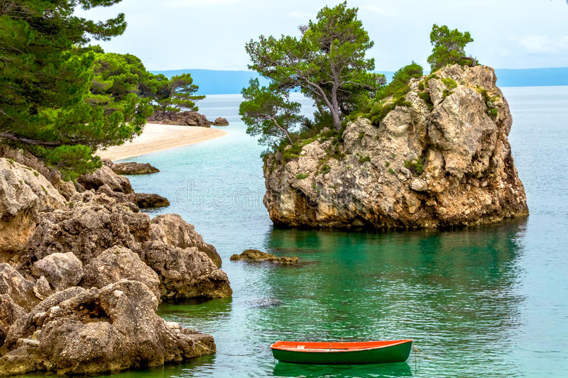 Landscape with rocky island and three on the beach. royalty free stock photography